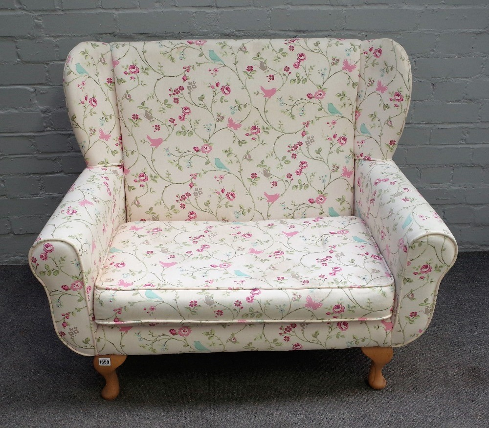 A modern child's wing back sofa, on squat cabriole supports with floral and bird print... Image