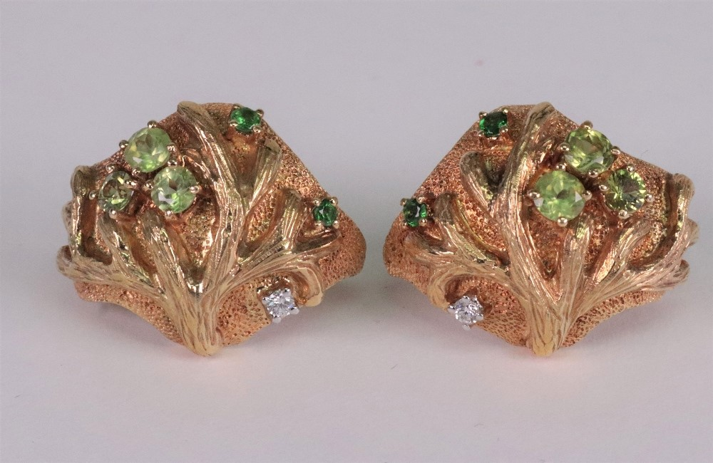 A pair of 18ct white and yellow gold green gem and diamond set earclips of abstract textured tree... Image