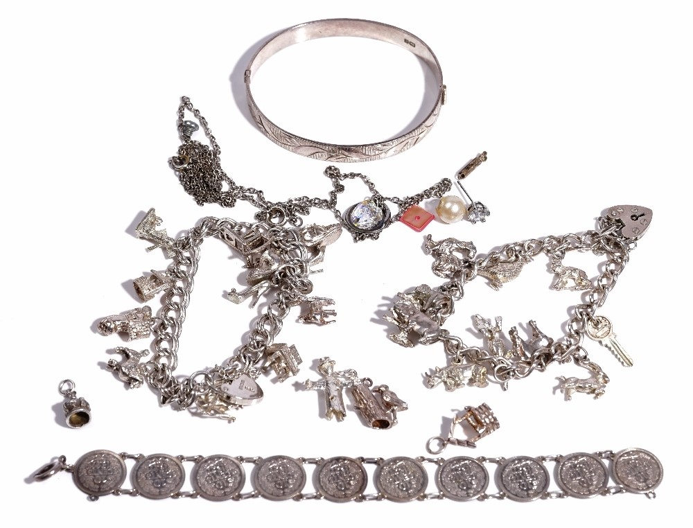 A silver curb link charm bracelet, fitted with eleven charms, including a crocodile, a horse and... Image