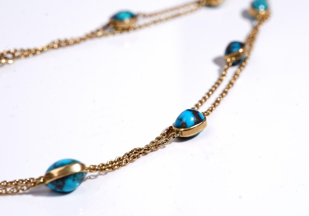 A gold and turquosie matrix long chain, the oval link chain spaced with collet set turquoise... Image