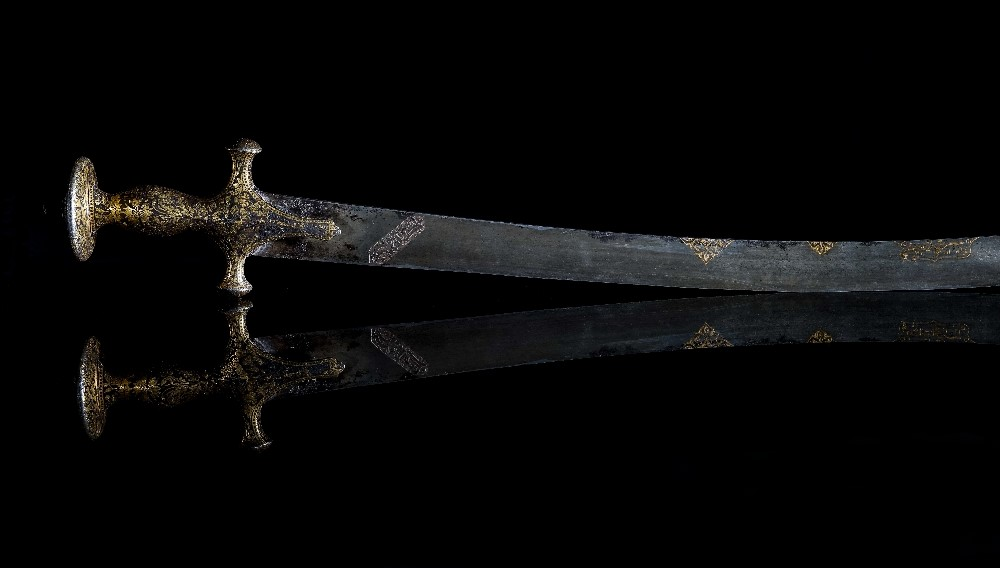 An early 19th century Indian gold inlaid Tulwar sword, with curved Damascened blade, the gold... Image