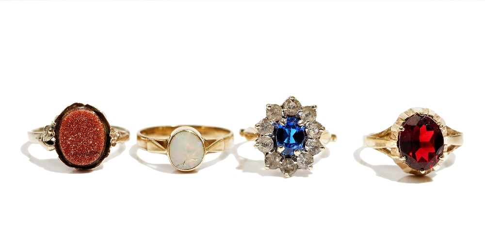 A gold ring mounted with an oval opal detailed '750', gross weight 2.5g, a gold ring mounted with... Image
