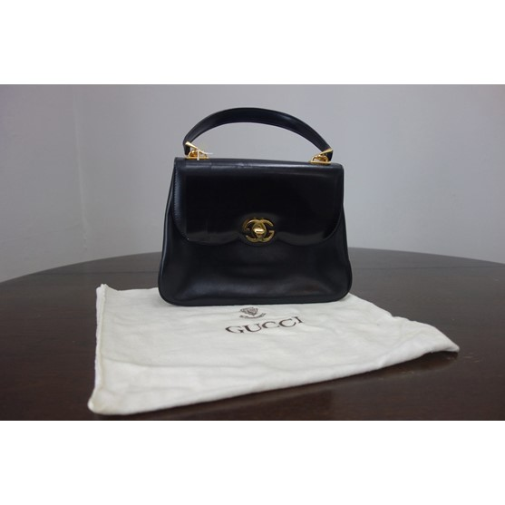 Gucci:  a lady's black leather handbag... Image