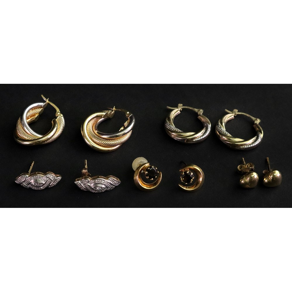 A collection of earrings including; a pair of bi-gold twist hoop earrings...