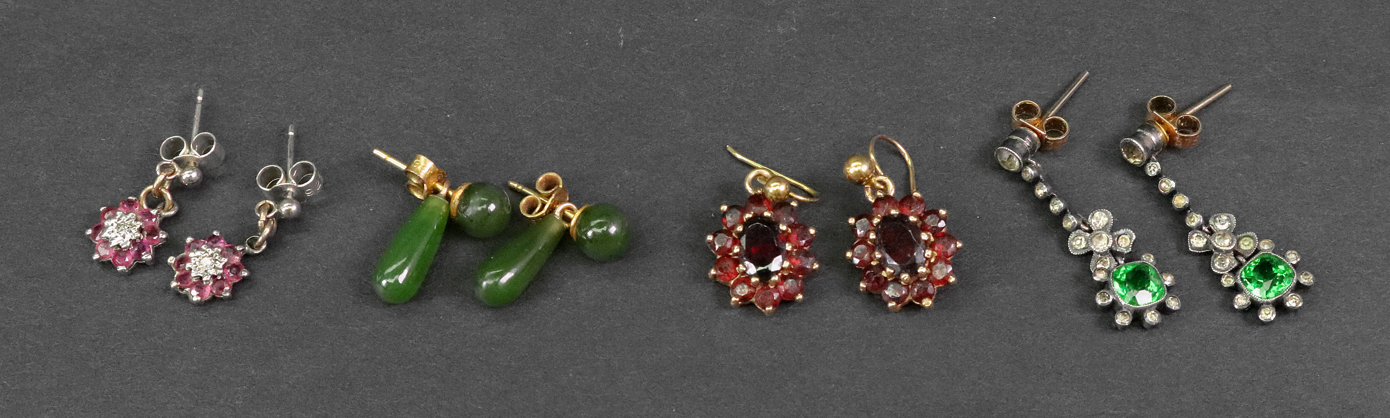 A collection of earrings, comprising: a pair of garnet cluster pendant...