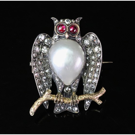 A late 19th/early 20th century diamond, pearl and ruby owl brooch, realistically formed, the body... Image